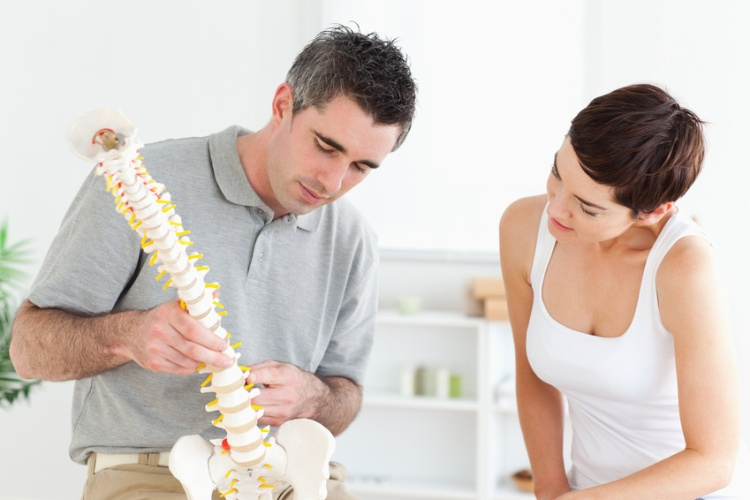 Chiropractor and patient looking at a model of a spine in a room